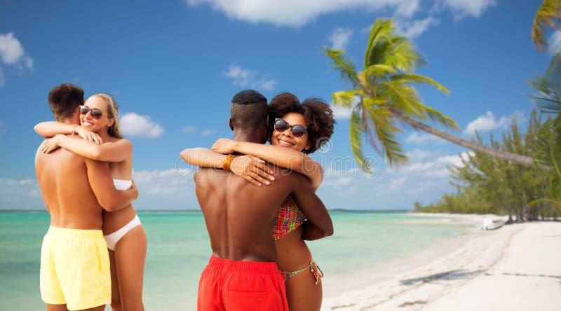 Счастливые друзья или пары обнимая на пляже лета стоковое изображение