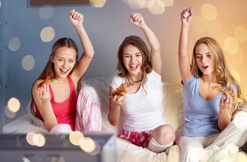 Счастливые друзья или предназначенные для подростков девушки есть пиццу дома стоковое фото