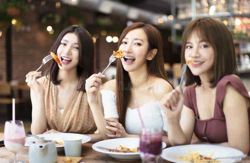 Счастливые друзья имея обедающий в ресторане стоковые фотографии rf