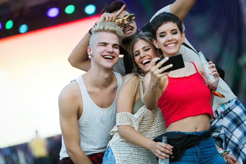 Счастливые друзья имея потеху на музыкальном фестивале стоковая фотография