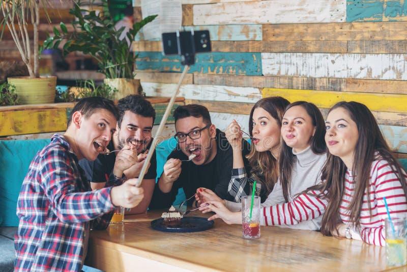 Счастливые друзья имея потеху совместно принимая selfie пока делящ шоколадный торт стоковое изображение rf