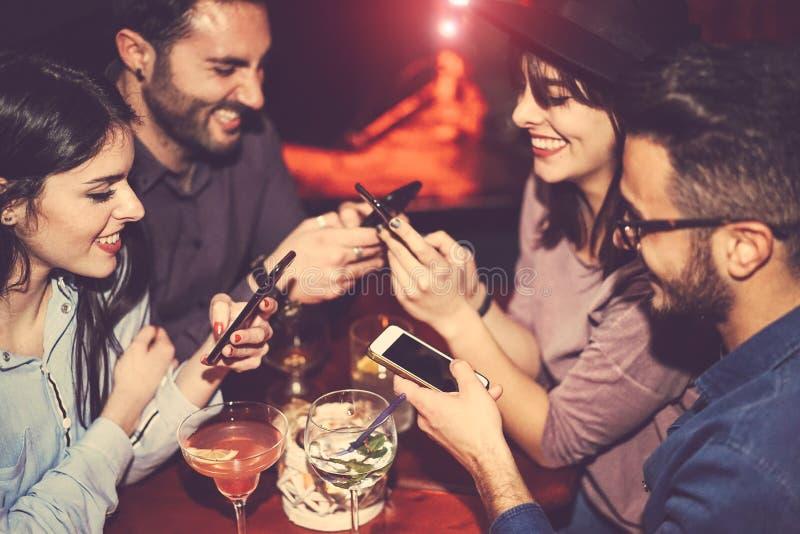 Счастливые друзья, которые пользуются мобильным телефоном и веселятся с коктейлями в джаз-баре - молодые люди, привыкшие к новым  стоковые фотографии rf