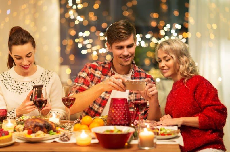 Счастливые друзья, которые устраивают рождественский ужин дома стоковые изображения