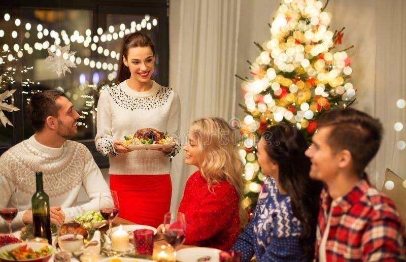 Счастливые друзья, которые устраивают рождественский ужин дома стоковая фотография rf