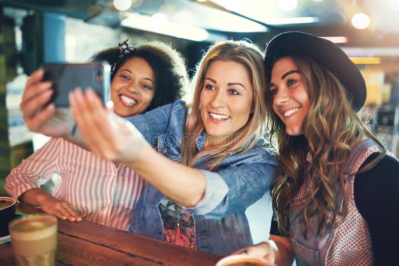 Счастливые друзья молодых женщин представляя для selfie стоковое фото
