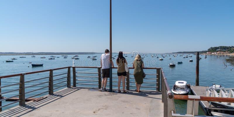Счастливые друзья на отдыхе в порту Кап-Феррет-Канон Аркачона во Франции смотрят на лодку и мечтают вместе стоковое изображение rf