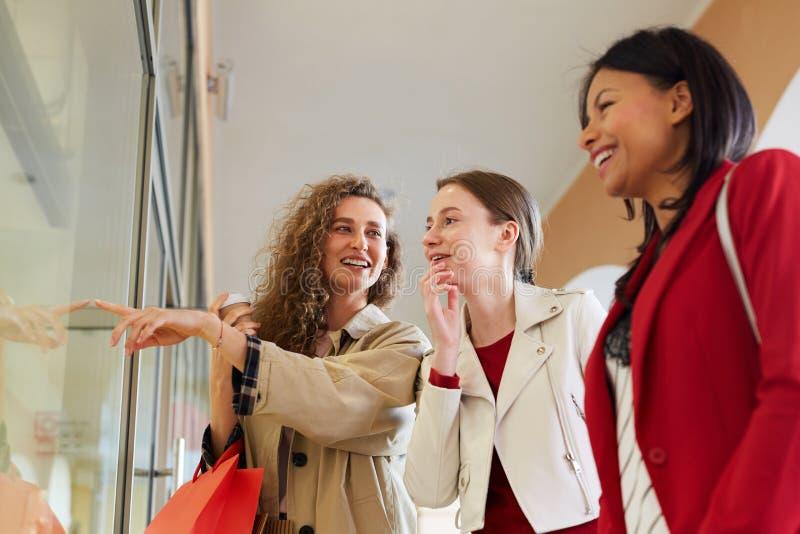 Счастливые друзья обсуждая моду в торговом центре стоковые изображения rf