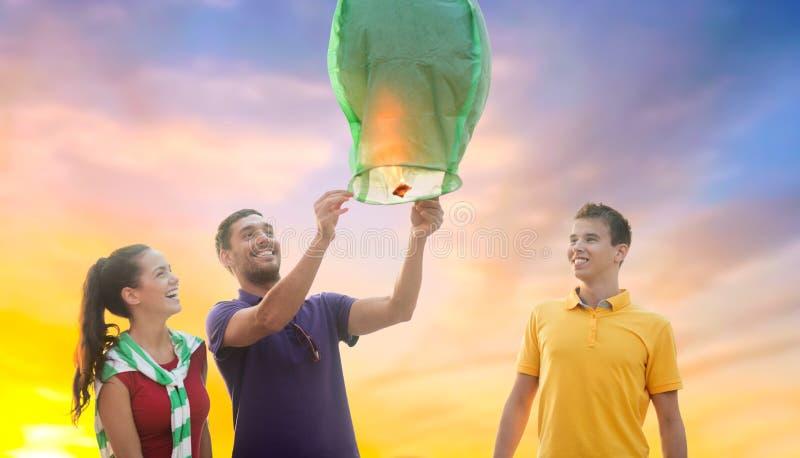 Счастливые друзья освещая китайский фонарик неба стоковое фото rf