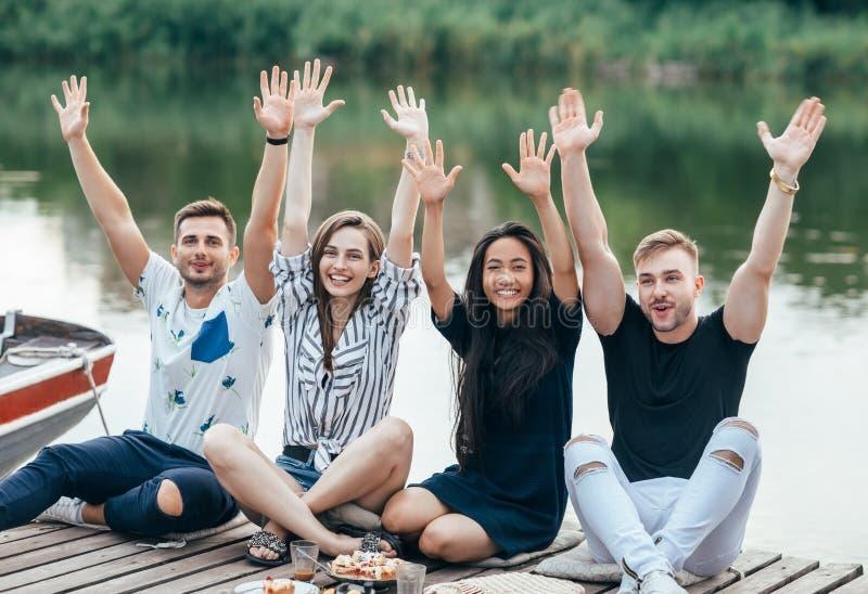 Счастливые друзья подняли руки ослабляя на пикнике outdoors на реке стоковые изображения