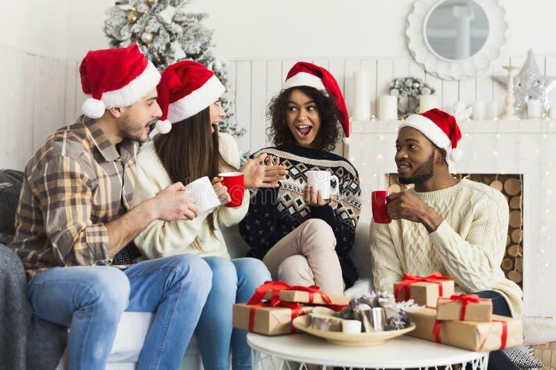 Счастливые друзья празднуя рождество дома стоковые фото
