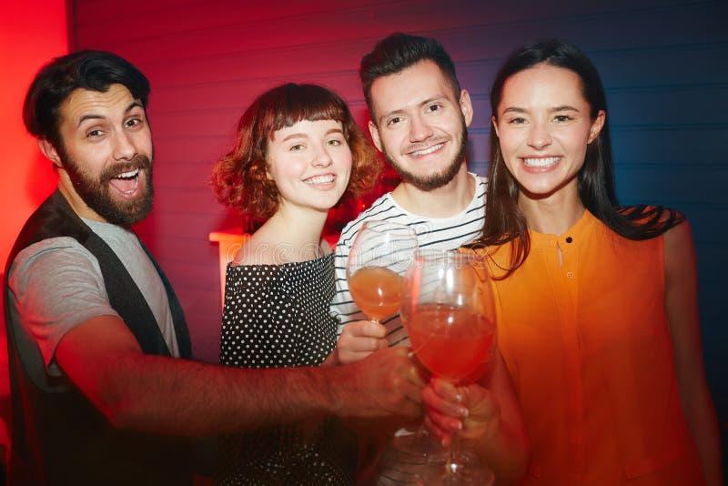 Счастливые друзья провозглашать на партии в красном свете стоковая фотография rf