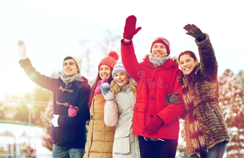 Счастливые друзья развевая руки outdoors стоковое фото rf