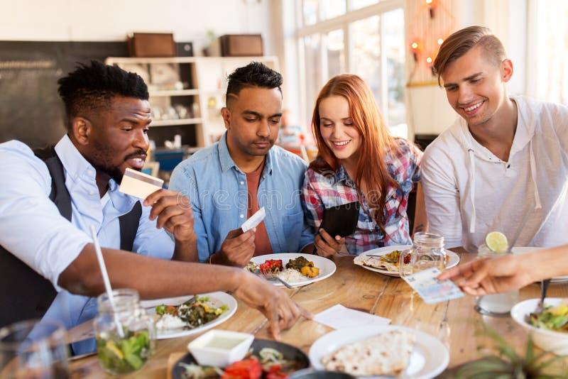 Счастливые друзья с счетом денег оплачивая на ресторане стоковая фотография