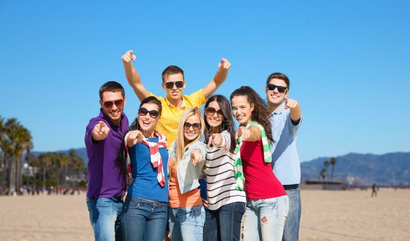Счастливые друзья указывая на вас над пляжем Венеции стоковое фото