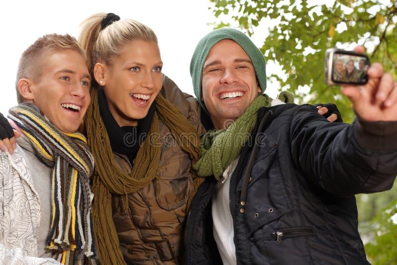 Счастливые друзья фотографируя в парке стоковые изображения
