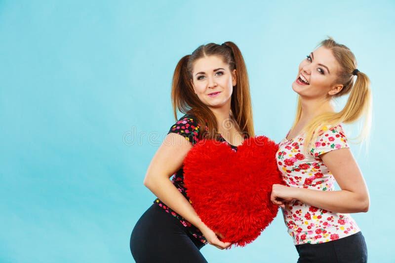 Счастливые 2 женщины держа подушку сердца форменную стоковая фотография rf