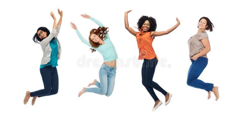 Счастливые женщины скача в воздух над белой предпосылкой стоковые изображения rf
