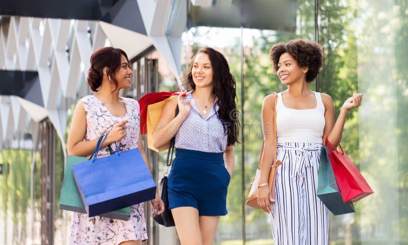 Счастливые женщины с хозяйственными сумками идя в город стоковые фотографии rf