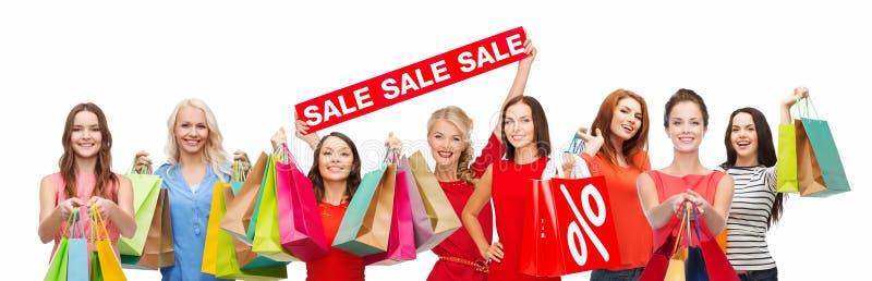 Счастливые женщины с хозяйственными сумками и знаком продажи стоковые изображения rf