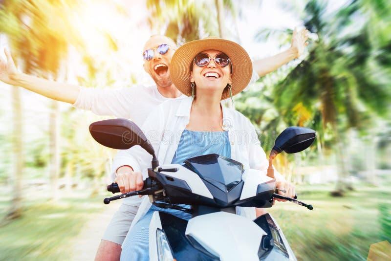Счастливые жизнерадостные усмехаясь путешественники пар ехать скутер мотоцикла под пальмами Тропическое изображение концепции кан стоковые фотографии rf