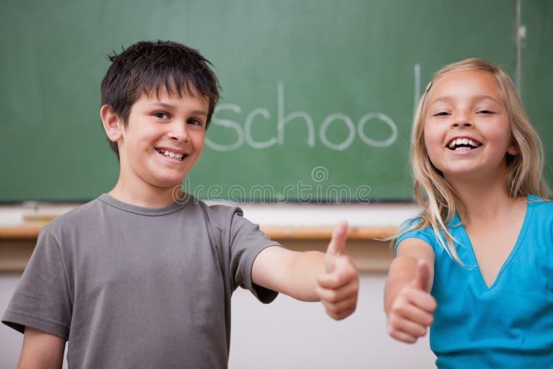 Счастливые зрачки представляя с большим пальцем руки вверх стоковое фото