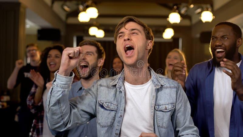 Счастливые зрители спички веселя для команды, восторга чемпионата, поддержки стоковое фото