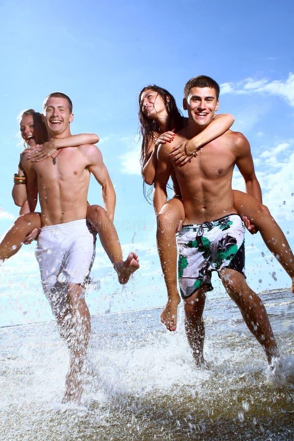 счастливые играя подростки моря стоковые фотографии rf