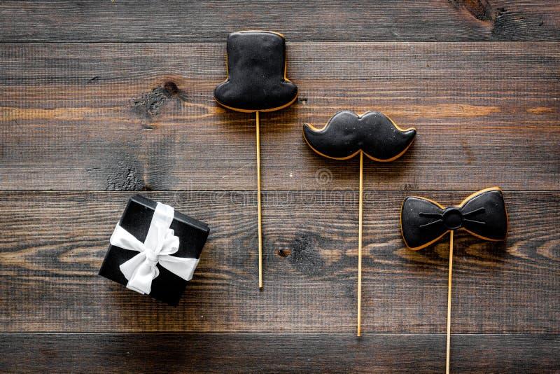 Счастливые карточки дня ` s отца Черный галстук, усик и печенья и подарок шляпы Деревянное взгляд сверху предпосылки стола стоковое изображение