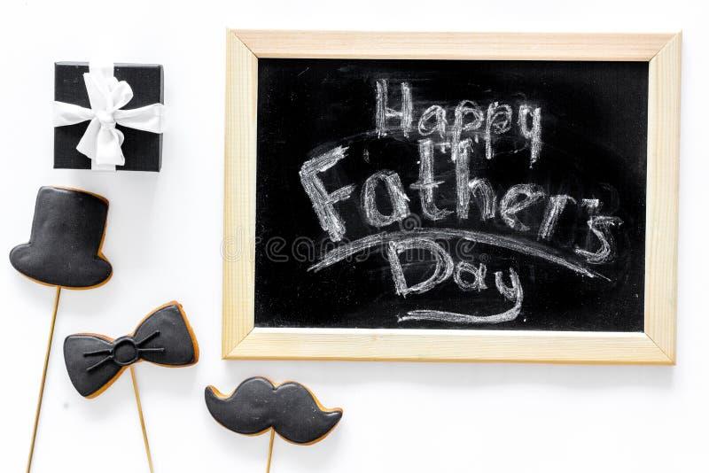 Счастливые карточки дня ` s отца Черный галстук, усик и печенья и подарок шляпы Белое взгляд сверху предпосылки стола стоковое фото