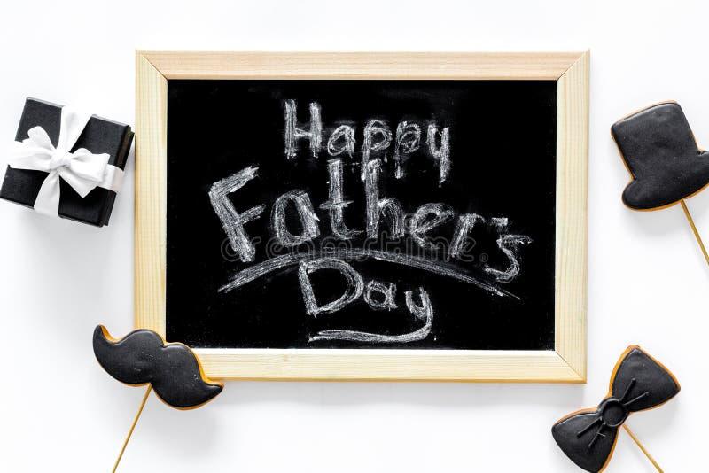 Счастливые карточки дня ` s отца Черный галстук, усик и печенья и подарок шляпы Белое взгляд сверху предпосылки стола стоковые изображения rf