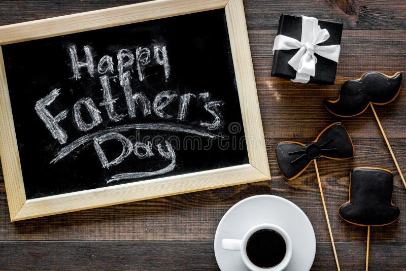 Счастливые карточки дня ` s отца Черный галстук, усик и печенья и подарок шляпы Деревянное взгляд сверху предпосылки стола стоковая фотография