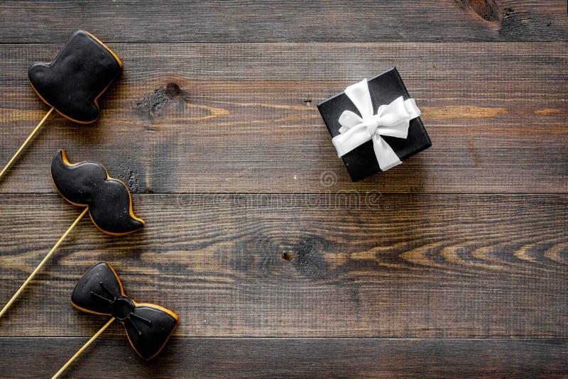 Счастливые карточки дня ` s отца Черный галстук, усик и печенья и подарок шляпы деревянный модель-макет взгляд сверху предпосылки стоковое фото rf