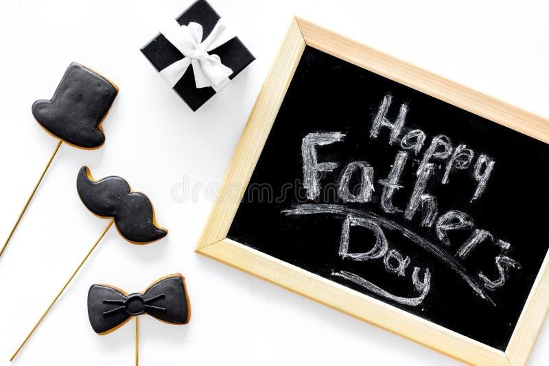 Счастливые карточки дня ` s отца Черный галстук, усик и печенья и подарок шляпы Белое взгляд сверху предпосылки стола стоковая фотография rf