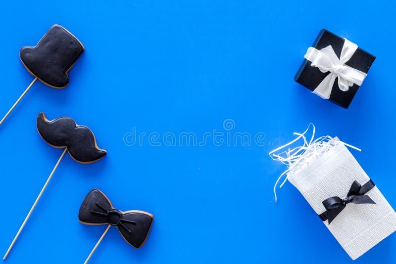 Счастливые карточки дня ` s отца Черный галстук, усик и печенья и подарок шляпы Голубое copyspace взгляд сверху предпосылки стоковые фотографии rf