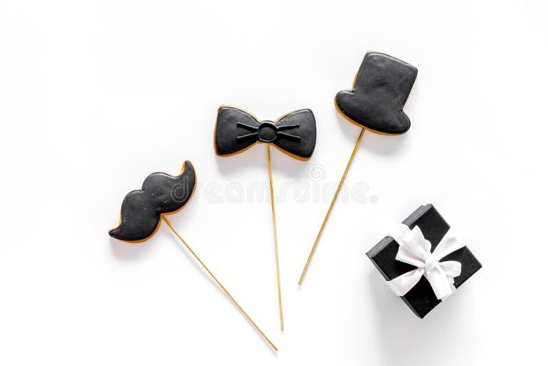 Счастливые карточки дня ` s отца Черный галстук, усик и печенья и подарок шляпы Белый модель-макет взгляд сверху предпосылки стол стоковые изображения rf