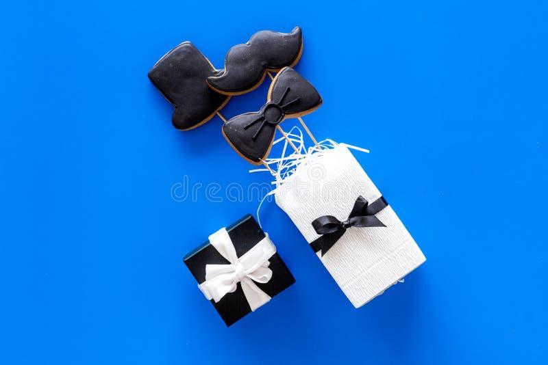Счастливые карточки дня ` s отца Черный галстук, усик и печенья и подарок шляпы Голубое copyspace взгляд сверху предпосылки стоковое фото rf