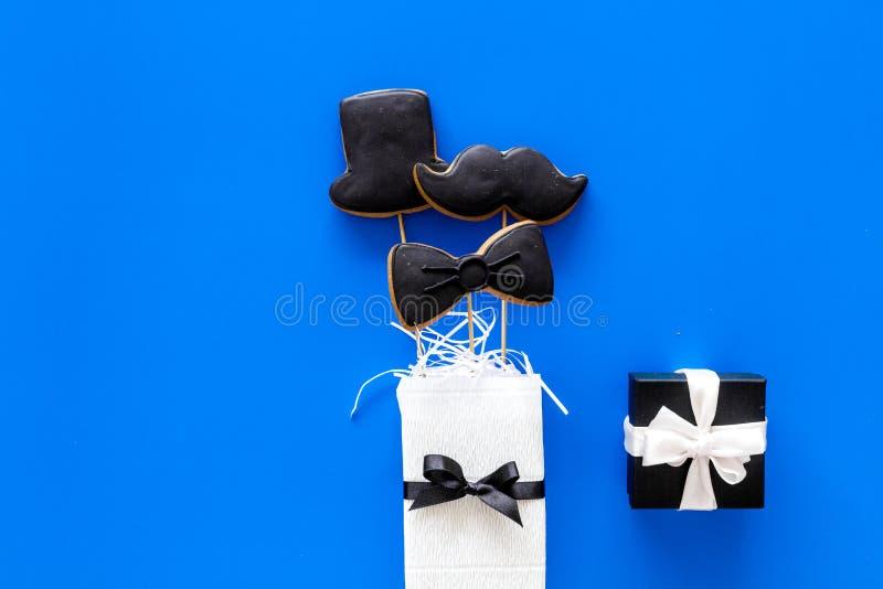 Счастливые карточки дня ` s отца Черный галстук, усик и печенья и подарок шляпы Голубое copyspace взгляд сверху предпосылки стоковое фото