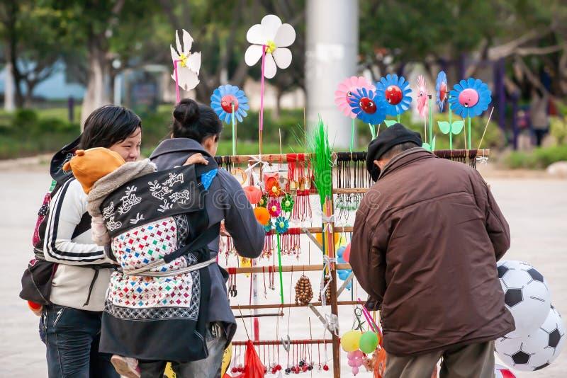 Счастливые 2 китайских матери с младенцами выбирая игрушки на стойле старшего мужского уличного торговца Сквер Nansa, Юньнань, юг стоковые изображения rf