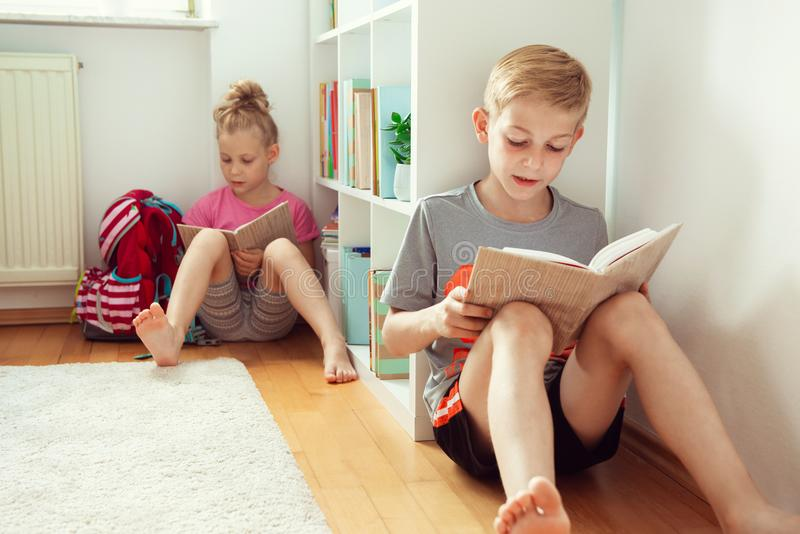 Счастливые книги чтения детей на поле на школьной библиотеке стоковые фото