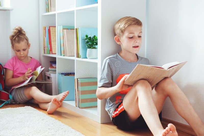 Счастливые книги чтения детей на поле на школьной библиотеке стоковые изображения rf