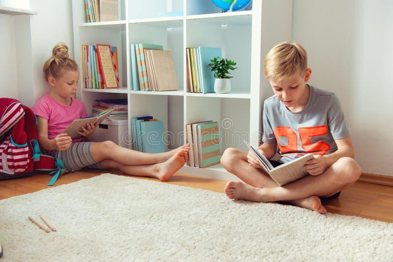 Счастливые книги чтения детей на поле на школьной библиотеке стоковые изображения