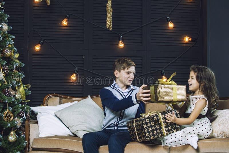 Счастливые красивые дети мальчик и девушка с подарками для того чтобы отпраздновать Ch стоковые изображения