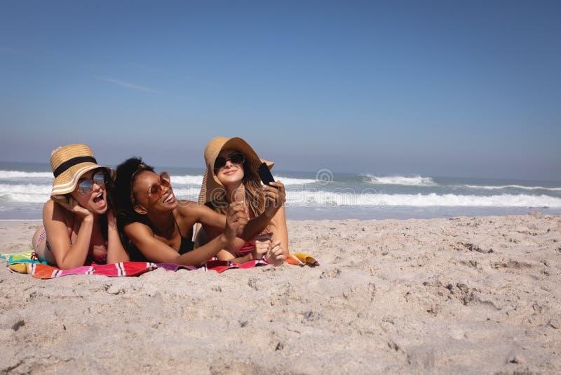Счастливые красивые молодые женщины со шляпой и солнечными очками принимая selfie на пляже стоковое изображение
