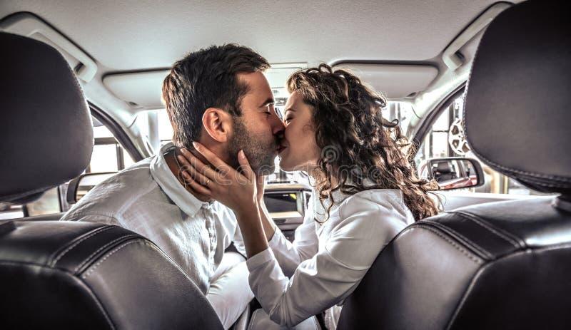 Счастливые красивые пары в любов целуя в новом автомобиле стоковое фото