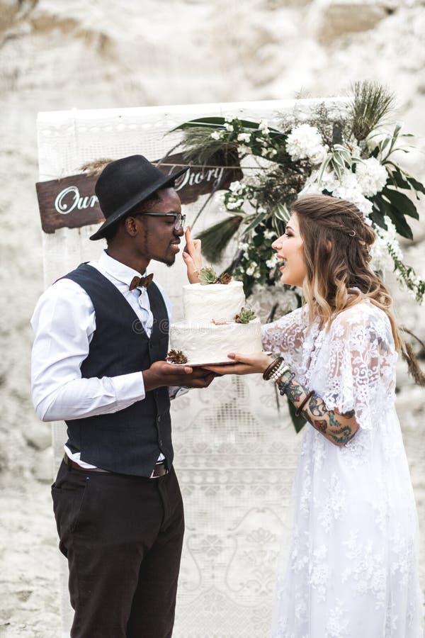 Счастливые красивые пары имеют потеху с украшенным свадебным пирогом с succulents в загородном стиле Свадьба Boho стоковое фото rf