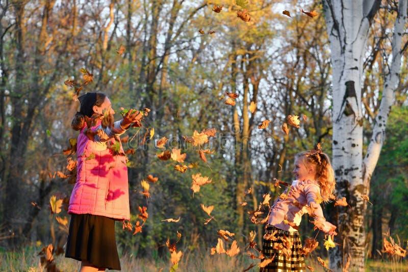 Счастливые листья осени хода мамы и дочери вверх в парке, радостной семье стоковое изображение rf