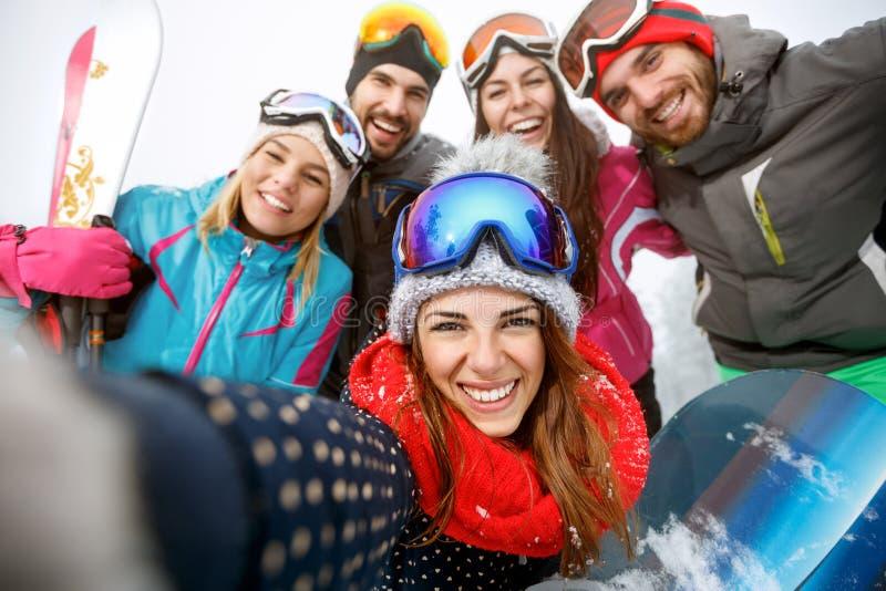 Счастливые лыжники на горе стоковое фото rf