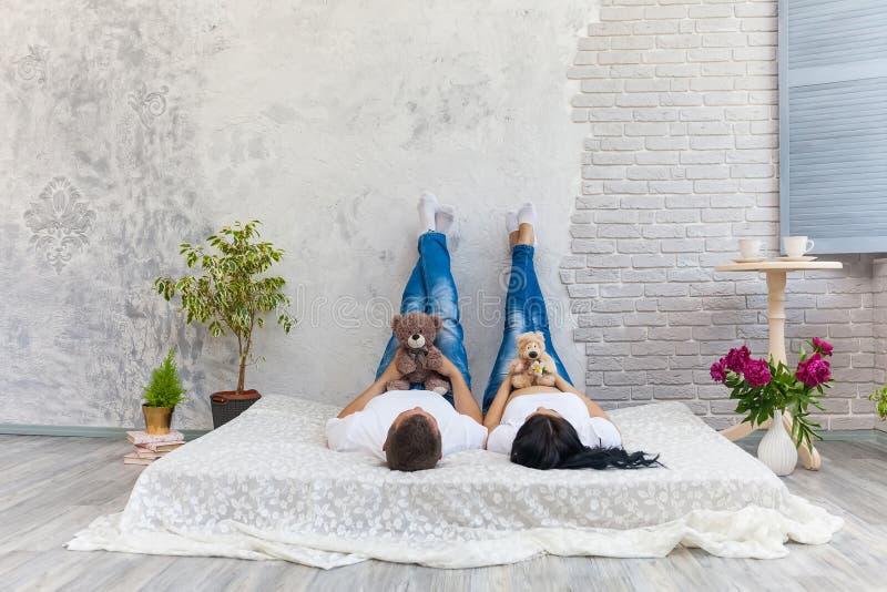 Счастливые любимые человек и беременная женщина дома стоковые изображения rf