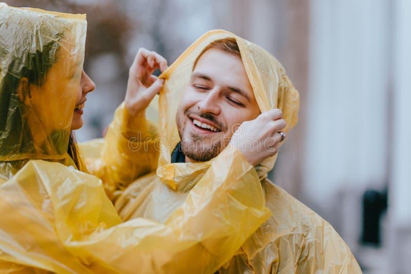 Счастливые любящие пары, парень и его девушка одетые в желтых плащах обнимают на улице в дожде стоковые фотографии rf
