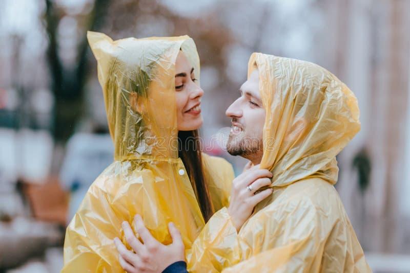 Счастливые любящие пары, парень и его девушка одетые в желтых плащах обнимают на улице в дожде стоковые изображения